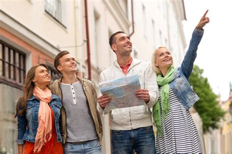 Group Of Smiling Friends With Map Exploring City Stock