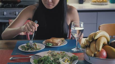 Girl eating salad in her kitchen dining room - Free Stock